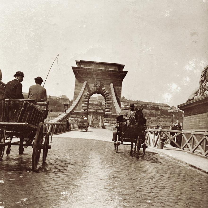 Kicsivel odébb, a Lánchíd pesti hídfője. Akkoriban még csak farács választotta el a járdákat a (baloldalon közlekedő) kocsik számára fenntartott útpályától. A merevítő fémszerkezet csak húsz évvel később kerül a helyére.