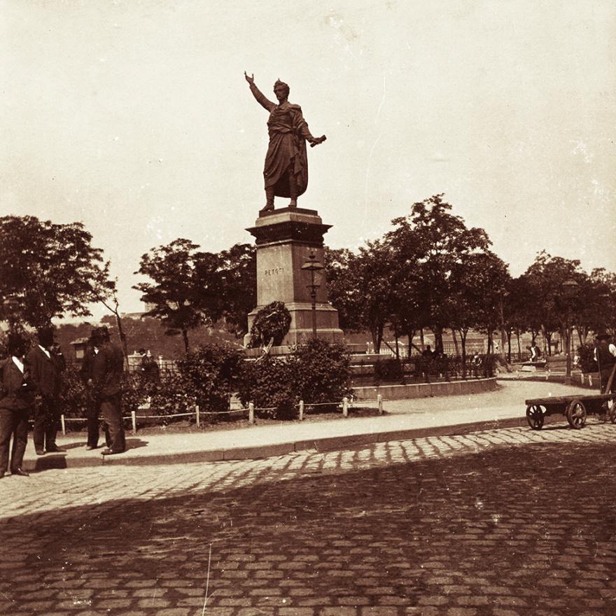Magyarország talán legismertebb Petőfi-szobra a fénykép készültekor még csak 12 éves volt, de nem csoda, hogy Kiss László meglátogatta. Izsó Miklós sokat vitatott tervei (egy majdnem négyméteres szobornak miért kell a levegőbe emelni a kezét? - kifogásoltak egyesek) Huszár Adolf valósította meg, az építészeti munkákat pedig maga Ybl jegyezte. A 22 évig tartó huzavona után helyére került alkotás kihúzta a dugót a palackból: utána sorra állították a Petőfi-szobrokat az országban.