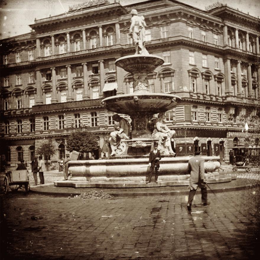 Teherhordó pihenteti hátikosarát a Danubius-kútra támasztva, középen pedig egy cilinderes úr pózol. Ez a Kálvin tér, melynek a képen látható elemeiből mára semmi sem maradt. Pedig a Dunát és mellékfolyóit ábrázoló kutat, s a mögötte látható bérpalotát egyaránt Ybl Miklós tervezte. Ez utóbbiban lakott amúgy ő maga is, ma Budapest egyik legjobban utált épülete, a Kálvin Center irodaház van a helyén.                          A világháborúban megrongálódott kutat viszont újrafaragták és az Erzsébet téren állították fel.