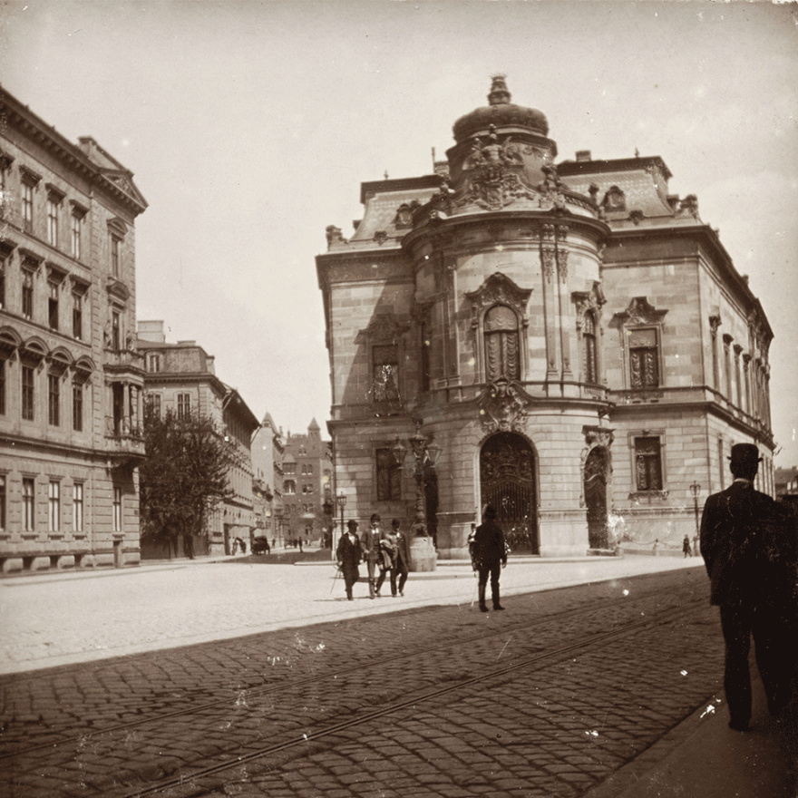 A mai tér névadója, Szabó Ervin még csak 17 éves volt a kép készültekor, akkoriban nem is volt neve ennek a közterületnek. Az épület pedig, mely ma a könyvtárnak ad otthont, Wenckheim Frigyes palotája volt. Mint minden valamire való képviselőnek, neki is kellett egy kis alkalmi szállás az akkori országház közelében, építtetett egyet hát magának. A villamos ugyan eltűnt azóta a Baross utcából, ám a villa előtti terecske kifejezetten előnyére változott az itt kialakított fasornak és a többi növénynek köszönhetően.