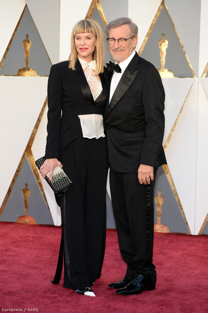 Kate Capshaw színésznő se néz ki túl csodásan férje, Steven Spielberg mellett ebben a kissé bohócos férfiszmokingban, de arra legalább jó, hogy átvezessen minket ez a kép a férfidivathoz