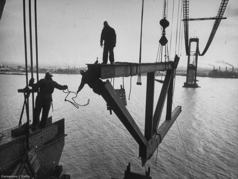 Veszélyes manőverekkel jár egy híd építése, itt éppen 5 méter magasban egyensúlyoznak egy hatalmas vasdarabon.