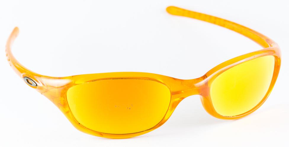 Oakley Fives (17gramm 35 ezer+)                         Az Oakley ősidők óta a sportszemüvegek nagyágyúja. A Fives elég régi, évek óta nem kapni, én is hónapokig nyomoztam a neten, mire valahol találtam, hogy aztán két-három év alatt, sok ezer kilométernyi felnyitott plexis motorozással tönkretegyem. Az egy dolog, kinek hogy áll, de látványos példa arra, hogy nem kell a technó rizsa, a karbon meg a kevlár, műanyagból is lehet 17 grammos napszemüveget készíteni. Ez aztán tényleg reggeltől estig hordható, akár motoron is, hiszen 100-120-as tempónál is jól véd a széltől. Arra is bizonyság, hogy a wraparound-univerzumban felesleges hatalmas légy-lencséket csinálni, hogy ne jusson be oldalt a fény. Sajnos az Oakley mintha leszokott volna ezekről a kisebb fazonokról, de ne legyen igazam.  A másik, ami miatt sírnom kell, valahányszor eszembe jut, hogy ráülés esetén nem törik el, hanem csak kipattan a szára. Csodálatos szerkezet, szerintem azért álltak le vele, mert egyszerűen túl jó volt. Tényleg: 17 gramm, jó aerodinamika, szép képű lencse - kit érdekel, ha úgy nézek ki benne, mint egy buckalakó?!