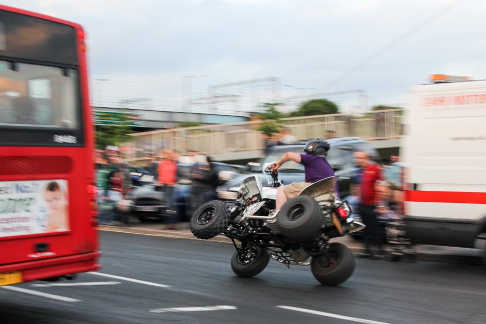 Mint láthatjuk, quaddal is lehet kétkerekezni. Igen, bukó nélkül is (tudom, itt épp van rajta), igen, gyerekkel hátul is, igen, a körforgalomban, egyenesen a kamionok között átmenve is. Szerencsére nem lett baja.