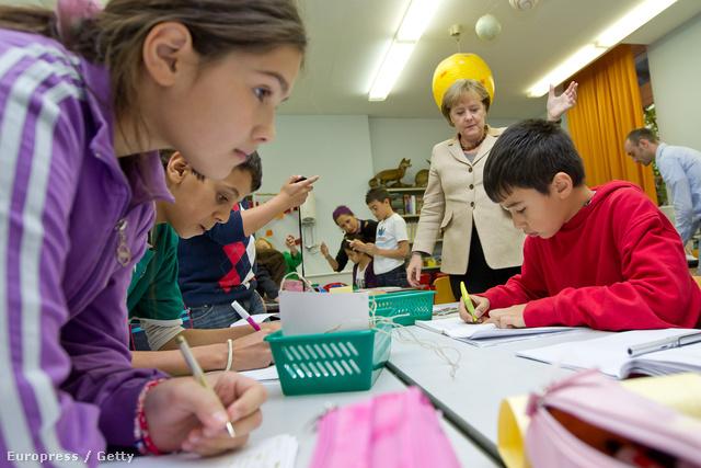 A képen Angela Merkel, német kancellár épp egy a bevándorlók gyerekeinek fenntartott iskolában tesz látogatást.