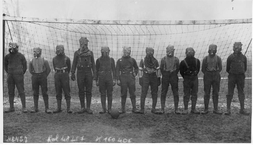 1916, Franciaország északi része. Egy brit katonákból álló rögtönzött focicsapat pózol a hadszintéren hevenyészve összerakott futballkapu előtt. Azt, hogy kivel játszották a kép elkészülte utáni meccset, és tényleg gázálarcban voltak-e, nem tudni, utóbbi erősen kétséges. A sportélet az I. világháború alatt és közvetlenül utána sem állt meg - a fegyverek a labdarúgást nem tudták legyőzni.