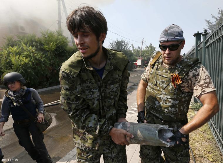 Oroszpárti fegyveresek cipelnek egy lőszer-maradványt Donyeckben