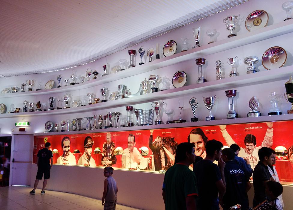 Á, ezek csak serlegek, bárki tud ilyeneket gyártani... Lent, piros háttér előtt, a vitrinben a híres ferraris F1-versenyzők sisakjai és szemüvegei az ötvenes évektől máig
