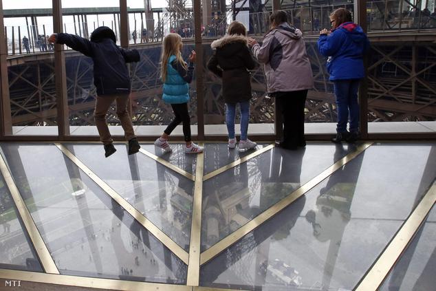 A párizsi Eiffel-torony felújított első szintjének új üvegpadlóján állnak látogatók