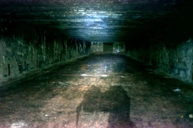 A halál csarnoka. Ebben a megközelítőleg hatvan méter hosszú és tíz méter magas csarnokban tárolták a taktikai atombombákat. Koromsötét volt idebent, a falakról megpörkölődve, kormosan kunkorodva mállik a vakolat mutatva, hogy itt komoly tűz tombolt valamikor. Kísérőnk szerint gumiraktár gyulladhatott ki itt valamikor.