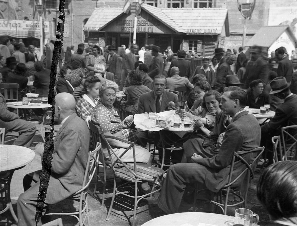 Az 1949-es Budapesti Őszi Vásár polgárinak tetsző látogatói sörrel és zsírpapírba csomagolt elemózsiával. Egy oszlopon még a Kossuth-címer látható, de azt néhány héten belül országszerte leváltotta a Rákosi-féle búzakoszorús, kalapácsos változat.