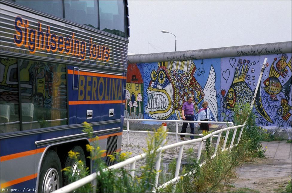 Turistabusz a fal tövében, aminek a felső emeletéről szinte át lehetett látni a túloldalra. A Nyugat-Berlinbe érkező turistáknak olyan nagy fa állványzatot is felállítottak a falnál, amiről átnézhettek, de pénzért át is lehetett látogatni rövid időre a túloldalra.