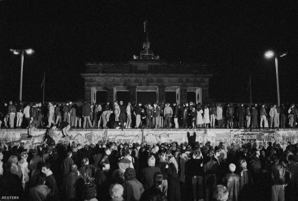 Együtt ünneplik a kelet- és nyugatnémetek a                          határnyitást a Brandenburgi kapunál. A párt vezetése leváltotta az NDK évtizedek óta államfő-párttitkárát, Erich Honeckert, utódja Egon Krenz lett. Végül a keletnémet vezetés a határok megnyitásáról döntött, amit a tervezettnél egy nappal korábban, 1989. november 9-én jelentettek be.