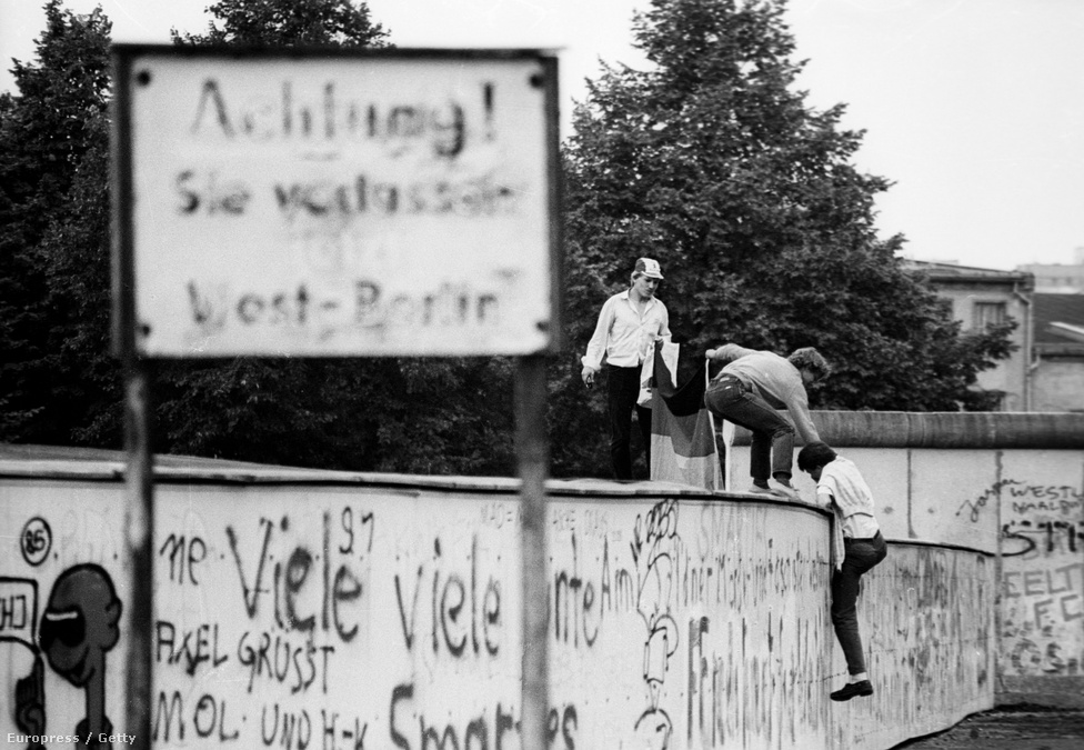 """""""Figyelem! Éppen elhagyja Nyugat-Berlint!"""" –                          hirdeti a tábla, miközben fiatalok éppen felmásznak                          a már graffitikkel tarkított falra 1989 nyarán. Évtizedek után a Szovjetunió gazdaságilag lényegében tönkrement a Ronald Reagan amerikai elnök által rákényszerített fegyverkezési versenyben, és Mihail Gorbacsov reformjai már elvezettek a Szovjetunió felbomlásához, és Kelet-Európában is beindították a rendszerváltó folyamatokat. A magyar határnyitással szeptemberben közel 13 ezer keletnémet menekült Magyarországon keresztül Ausztriába, ezt pedig több keletnémet városban is állandósuló tüntetések követték."""