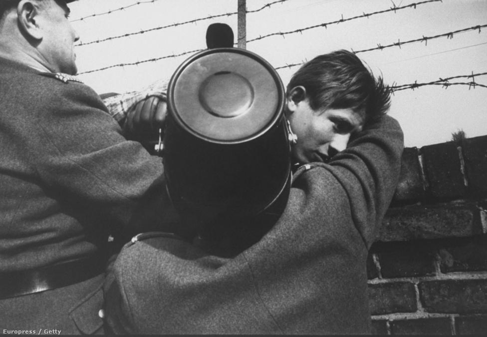 Két nyugatnémet rendőr segít át egy 17 éves fiút                          a falon. A becslések szerint a fal fennállásának 29 éve alatt körülbelül tízezren próbáltak meg átszökni Nyugat-Berlinbe, és 5000-en járhattak sikerrel.