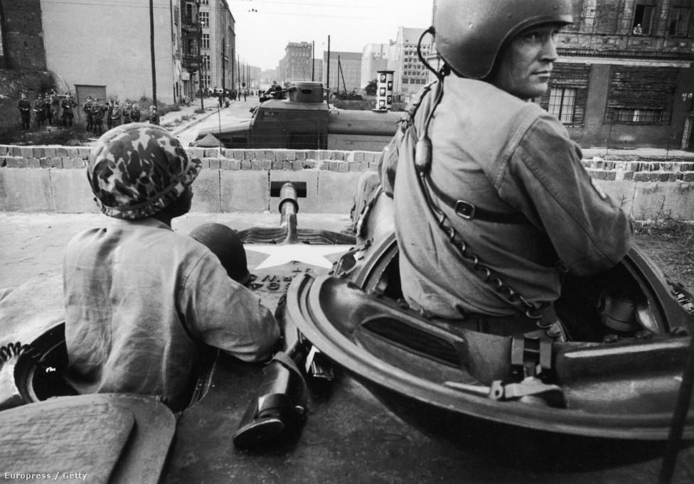 Német katonák a frissen felhúzott fal két                          oldalán. Ekkortól 29 éven át néztek farkasszemet                          egymással. 1961. augusztus 13-án, vasárnap a                          berliniek arra ébredtek, hogy éjszaka a villamos- és metróvonalakat átvágták, az utcákat drótkerítéssel zárták le, árkokat kezdtek ásni, amit fokozatosan egész Nyugat-Berlin körül fallá emeltek.