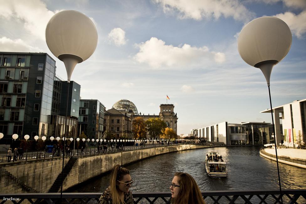 Az évforduló alkalmából Berlin belvárosában 15 kilométeres szakaszon jelölték ki fehér lufikkal az egykori fal helyét, aminek a teljes hossza amúgy 160 kilométer volt. Látható, hogy a Spree folyó mindkét partján fal állt, a háttérben álló  Reichstag így 1989-ig Nyugat-Berlin legszélét jelentette. A folyón őrhajók járőröztek, a víz alatt dróthálókkal és veszélyes akadályokkal próbálták megakadályozni, hogy valaki úszva próbáljon átjutni nyugatra. Előfordult, hogy a nyugatnémet újságírók a másik oldalról fotózták, amint az NDK-s határőrök kihalászták a vízből egy menekülő holttestét.