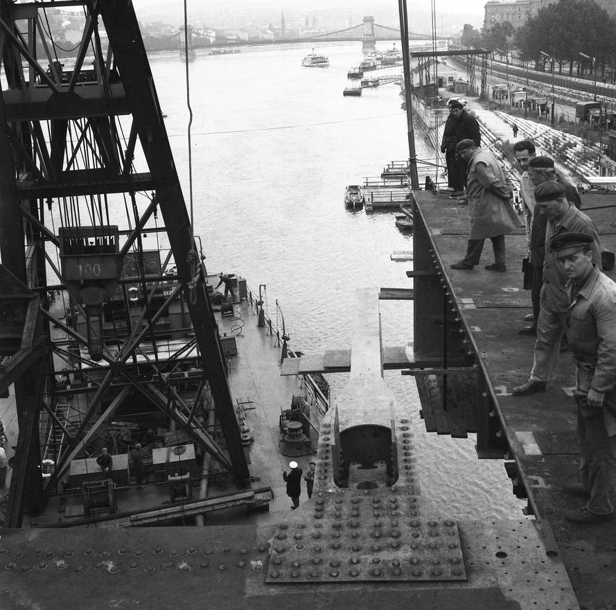 Az Erzsébet híd építése, az utolsó előtti pályaegység beemelése a pesti hídfőnél, háttérben a Lánchíd, 1964. A 100 tonna súlyú, 10 m hosszú, 20 m széles hídszakaszokat az Összekötő vasúti híd előtt elhelyezkedő szerelőtelepen állították össze, majd úsztatták az épülő hídhoz.