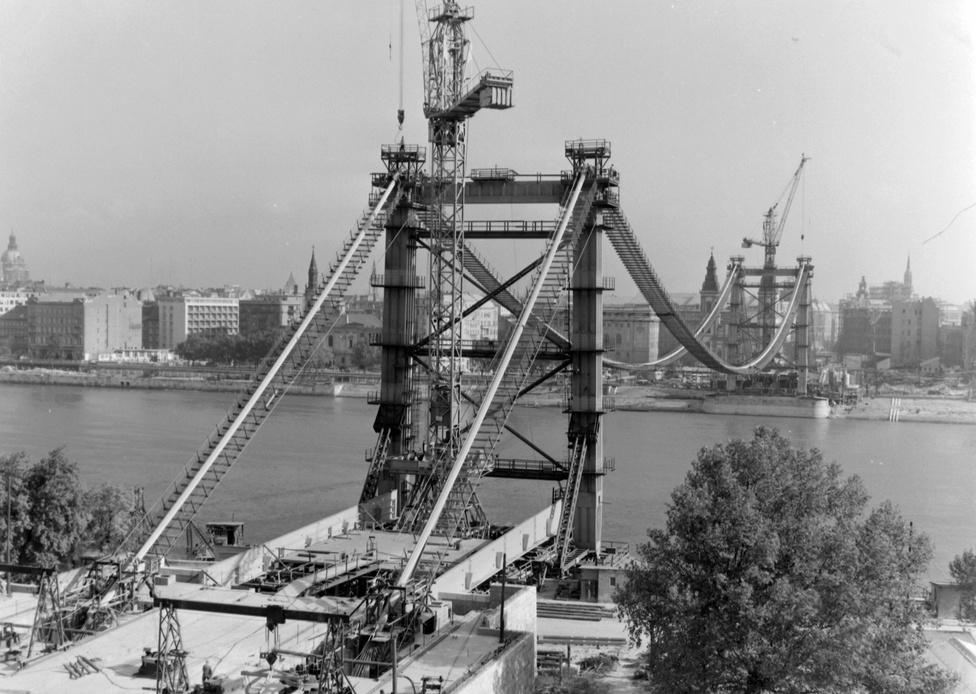 Az épülő Erzsébet híd a Gellérthegyről nézve, 1963. A két tartókábel egy-egy kábelkötege 61 darab elemi kábelből van összeállítva. A helyszíni acélszerkezet szerelési munkái 1962 szeptemberében kezdődtek, az iránykábelt 1963 júliusában húzták át, októberre az utolsó kábel is a helyére került.