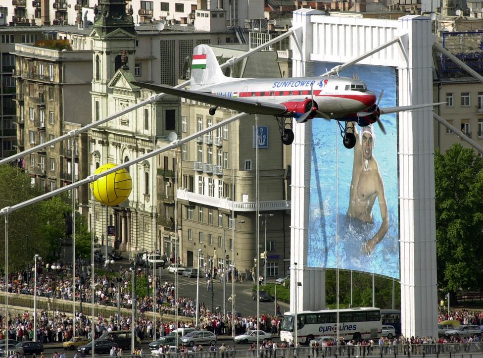 Egy Li-2-es matuzsálem repülőgép elrepül az Erzsébet híd felett a Magyarország Európai Uniós csatlakozása alkalmából rendezett légifelvonuláson, 2004. május 1. A gépet 1939 és 1952 között gyártották a Moszkva melletti Himkiben, illetve Taskentben, miután a második világháborús német támadás miatt evakuálni kellett a gyárat. A Liszunov Li-2-est a szovjetek az amerikai Douglas DC-3-as gyártójától vett licensz alapján fejlesztették ki. Ezek a gépek (öt darab) voltak a második világháború utáni magyar polgári légiközlekedés első repülőgépei, és nem a Szovjetunióból, hanem Romániából érkeztek. A Malév 1954-ben alakult, miután kivásároltuk a szovjetek részét az addigi közös légitársaságból, a Maszovletből. A kép készítésének időpontjában a Malév még zömmel belföldre, például Szegedre, Szombathelyre, Győrbe járt, a bécsi járat csak 1956-ban indul meg. A forradalom leverése után egy évig a szovjetek minden repülést betiltottak, az első újraindult járat a Budapest-Miskolc-Debrecen volt.