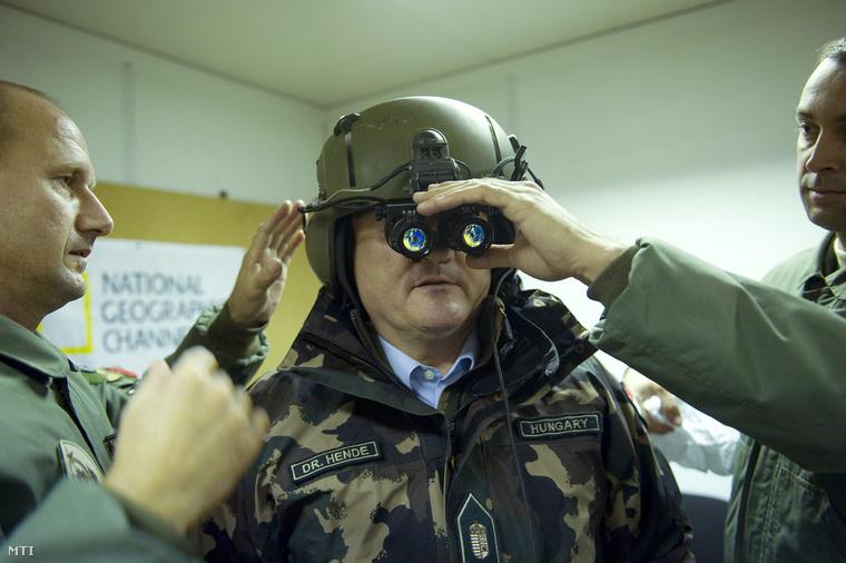 Hende Csaba honvédelmi miniszter kipróbál egy éjjellátó-készüléket egy éjszakai gyakorlat előtt a honvédség táborfalvai kiképző bázisán.