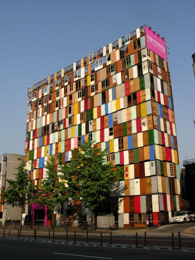 Összeállításunk egyik kakukktojása az 1961-es születésű Dél-koreai építész és dizájner munkája, Choi Jeong-Hwa ugyanis több ezer színes ajtóval fedte borította be egy tíz emeletes épület homlokzatát a koreai köztársaság fővárosában.