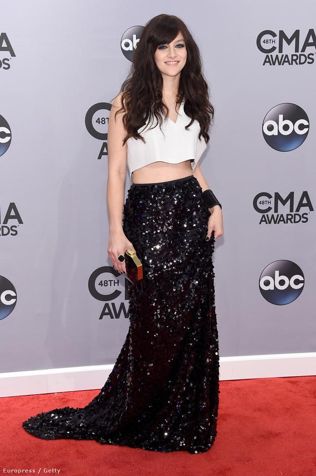 A 21 éves színésznőként és énekesnőként ismert Aubrey Peeples egy fehér hasvillantós felsőt vett fel földig érő fekete, flitteres szoknyájához, melyben igencsak modern hatást keltett a 48. CMA díjátadó vörös szőnyegén.