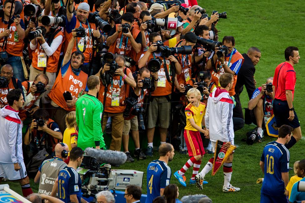 A brazil vb döntőjén az egyik kísérő az arénába lépve visszafordul a mögötte haladó társához és az arcáról egy pillanatra leolvasható a vb-döntő miatti izgatottság.A pálya mellett a vb-meccseken kb. 250 fotós dolgozik. Ennél sokkal többen akartak bejutni a mérkőzésekre, így a bekerüléshez egy sor előzetes regisztráció mellett elég fontosnak is kellett lenni ahhoz, hogy valaki helyet kapjon. Az Origo fotósaként nem tartoztam a kiemelt sajtótermékek közé egy brazil-német döntőn, de nem adtam fel. Kimaradtam az első körből, aztán beálltam a több száz várakozó fotós közé, akik között a fennmaradt helyeket sorsolták ki. Kora reggeltől sorban álltam, de még a meccs előtt fél órával sem volt helyem a stadionba. Az utolsó 12 helyre egyesével sorolták a neveket, és 150 izgatott fotós várta, hogy elhangozzon a sajátja is. Ebből a körből is kimaradtam, de ekkor kisebb csoda történt: felengedtek minket az egyik távolabbi szektor üres székeire. Pocsék hely volt, nem is lehetett igazán jó képeket csinálni onnan, de mégis végtelenül boldog voltam, mert megérte egész nap könyökölni, furakodni és izgulni. Azt hiszem, úgy mosolyogtam én is végig a meccset, mint a srác a képen.