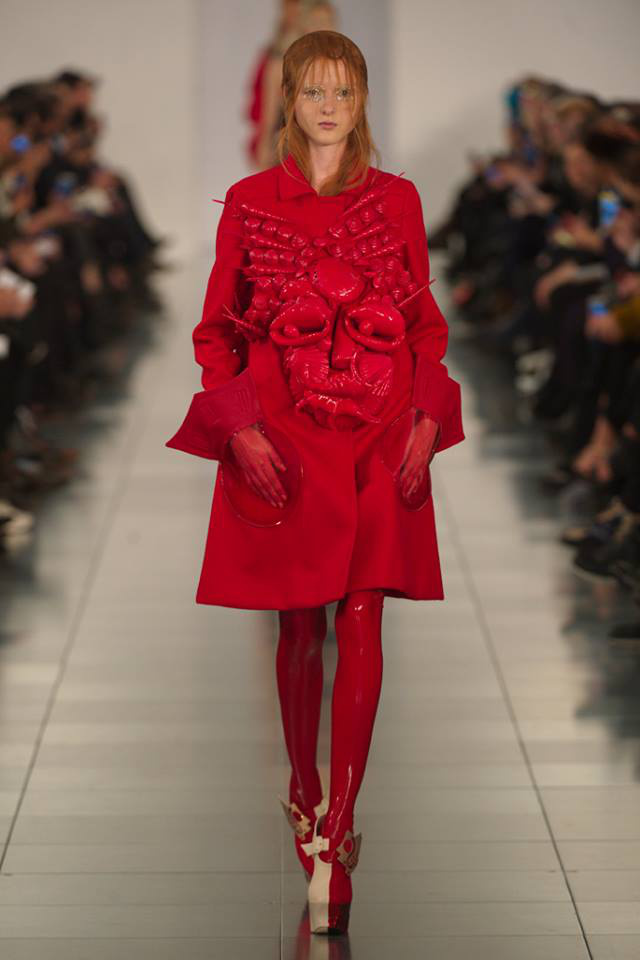 Piros színű A-vonalú kabát kagyló-szerű arccal díszítve,  PVC zsebekkel, latex harisnyával és Mary-Jane platform cipővel Maison Margiela kifutóján.