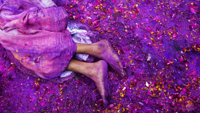 Egy hindu özvegy fekszik a földre hintett színes porfestékben, a Holi ugyanis az újjászületés szimbóluma is.