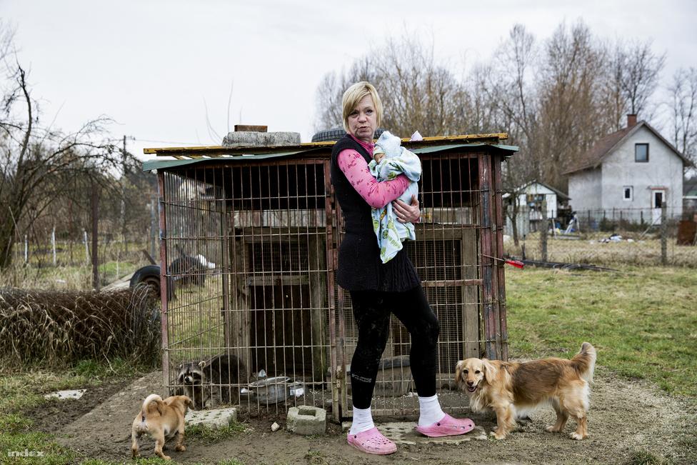 """Edina 46 éves, van egy felnőtt fia, egy Budapest-környéki település tanyáján él 17 kutyával, egy mosómedvével és a férjével. Volt már bábszínész, óvónő, most pedig egy kutyamenhelyen dolgozik, a tanyán pedig mentett kistestű- és kölyök kutyákat lát el. Körülbelül 10 éve, az eBayen látott először reborn babát, és azonnal szeretett volna egyet. Mivel nehéz anyagi körülmények között él, babáinak az árát az élelmiszerre szánt pénzből spórolta össze. """"A férjem kamionos, amikor külföldre megy, mindig hagy itt pénzt ennivalóra, abból teszek félre 500-1000 forintonként"""". Edina kilencszer várt kisbabát, de csak egy született egészségesen, élve közülük. Edina a barátai szerint az élethű babákkal pótcselekvést végez, gyakran nevezik betegnek emiatt. De őt nem zavarják a negatív vélemények, szeret babázni, rendszeresen öltözteti, pelenkázza a kicsiket. Adományokból rengeteg babaruhája, hordozója és babakocsija is van, abban szokta tologatni babáit. A fotón Csegőt tartja a mosómedve ketrece előtt, másik babája, Panka éppen hajmegújító beültetésen a készítőjénél van."""