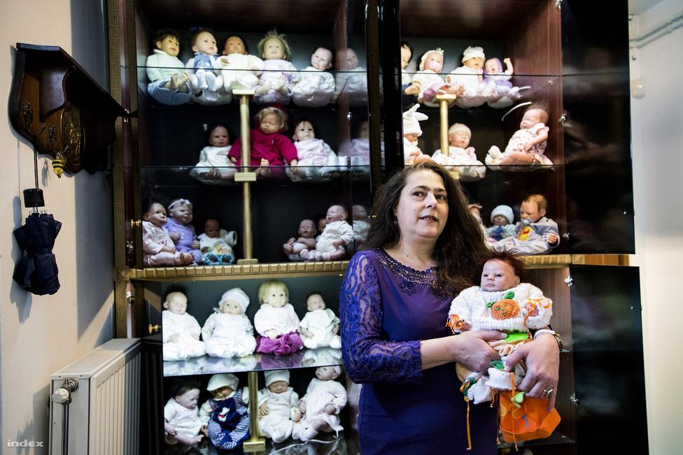 """""""Nem fürdetem, nem öltöztetem őket, azt olyanok csinálják, akinek nincs gyereke."""" Mégis, komoly kiegészítőgyűjteménye van hozzájuk, egy gardróbszoba megtelt a több váltás ruhával, babakocsikkal, hordozókkal, azt mondja, ezeket a kiállításra vette. """"Gyerekkoromban összesen egy babám volt, egy csodálatos porcelánbaba, gyűjtögettem a zsebpénzemet, hogy pelenkát vehessek neki. Aztán felnőttként, amikor megtehettem, megvettem mindent, ami megtetszett"""" - mondja nevetve, miközben simogatja a kezében lévő Taylor haját, elrendezi mágneses cumiját és a ruháit."""