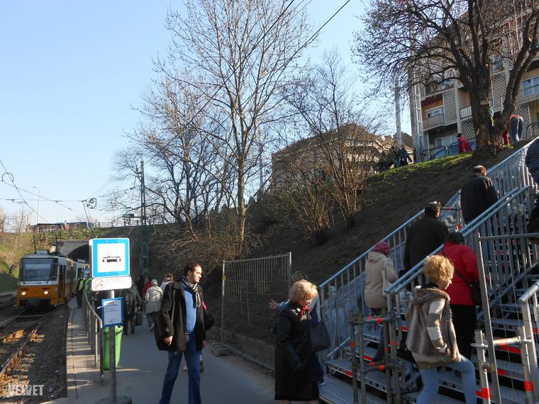 Az emberek pedig megmásszák az ideiglenes fémlépcsőket.