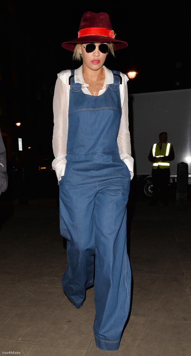 Rita Ora átlátszó fehér blúzzal és piros szalaggal átkötött kalappal kombinálta bő szárú kezeslábasát.