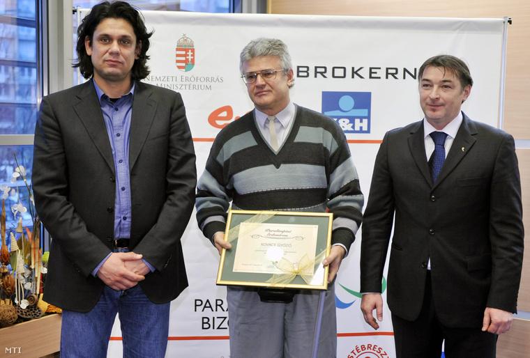 Kovács Győző asztalitenisz-edző Paralimpiai Érdemérmet tart a kezében, amelyet Gömöri Zsolttól, a Magyar Paralimpiai Bizottság (MPB) elnökétől (j) és Deutsch Tamás alelnöktől (b) vett át az (MPB) közgyűlésén a Sportok Házában (2011. november)