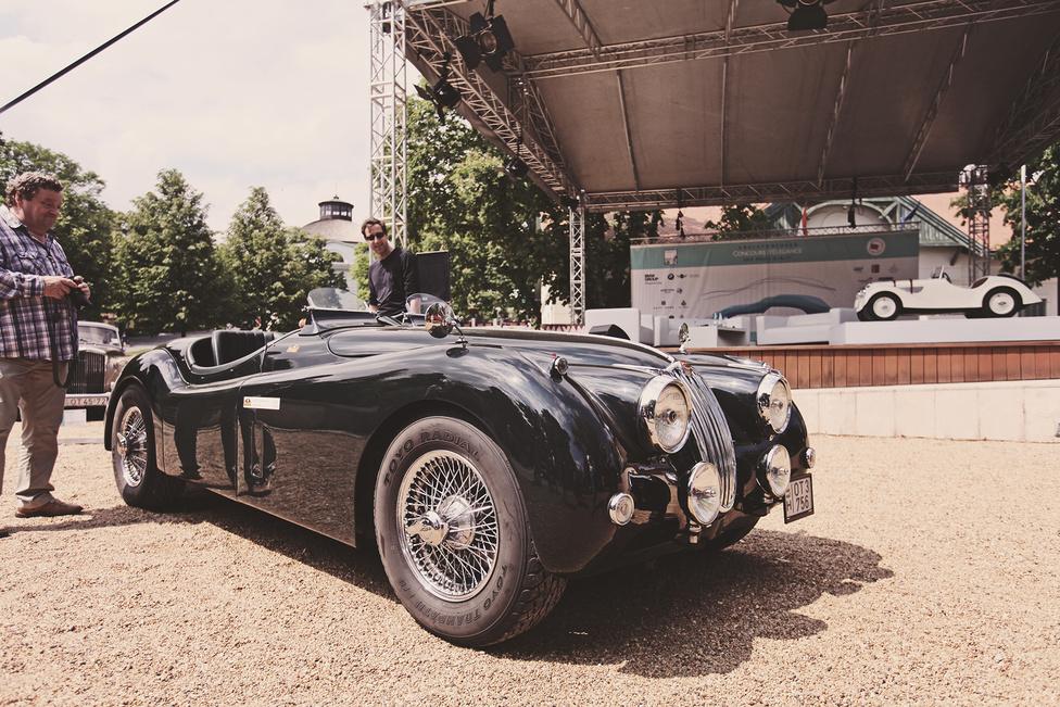 A tavalyi Concours d'Elegance győztese ez az 1956-os Jaguar XK 140 Roadster, amely nem csak kiállításokon mutatja meg magát, hanem évről évre részt vesz az Oldtimer Szuperkupa versenyein is. Némi korhű optikai tuning teszi még izgalmasabbá, a lökhárítók helyett csak két ködlámpa díszíti az orrát és a nagy szélvédő helyett csak két kis szemüveglencse tereli el a menetszelet a vezető és utasa elől.