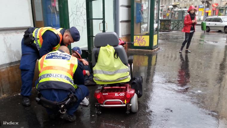 Két rendőr az esőben is nekiállt megszerelni egy defektes kerekesszéket