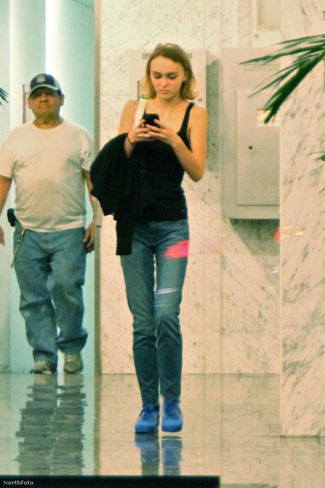 Johnny Depp lánya telefonjába teljesen belefeledkezve készül elhagyni egy épületet.