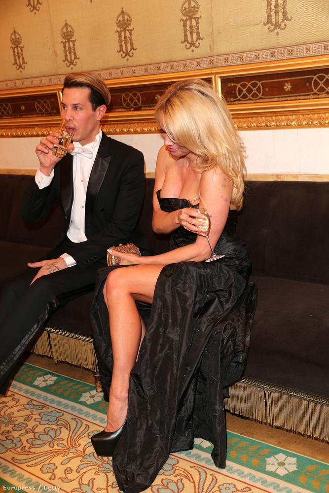 Közben rájöttünk! Pamela Anderson azért nyűgös, mert a világ legbonyolultabban hordható ruhájában érkezett az eseményre, amelyet az egyik kezével folyamatosan tartania kell, ha nem szeretné, hogy előhulljanak a mellei