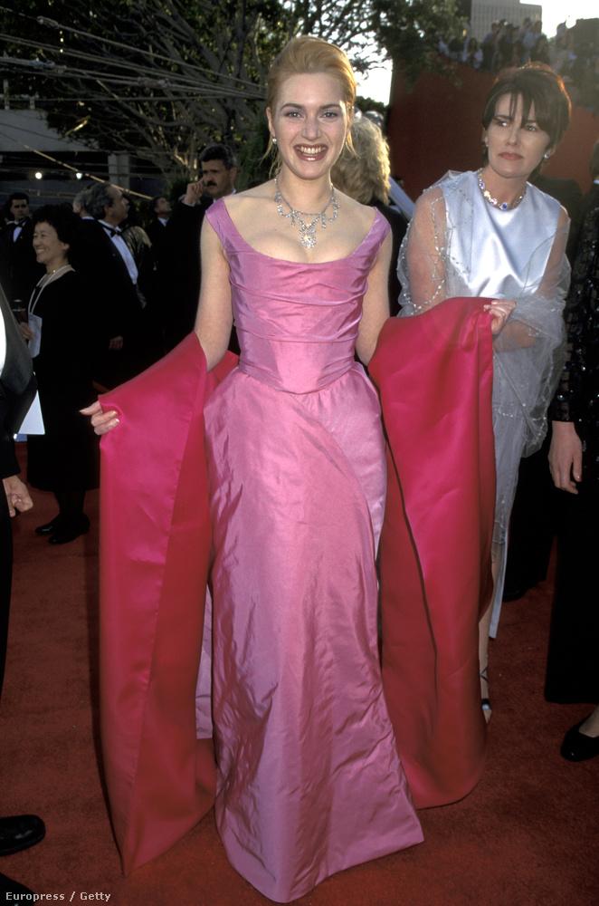 Divatos ruháját a mögötte érkező asszony is elismeréssel figyeli.