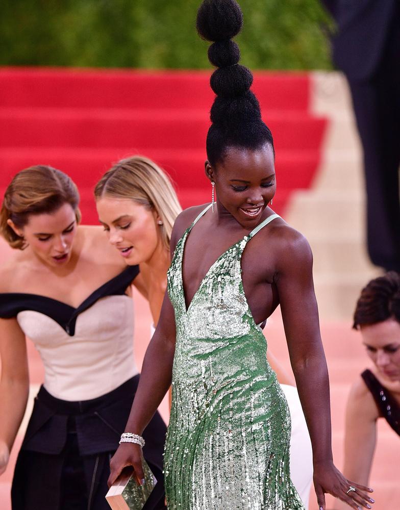 Másoknál is okozott problémát a ruha: balról jobbra Emma Watson, Margot Robbie és Lupita Nyong'o színésznők igyekeznek óvatosan lépni, miközben utóbbit igazgatják.