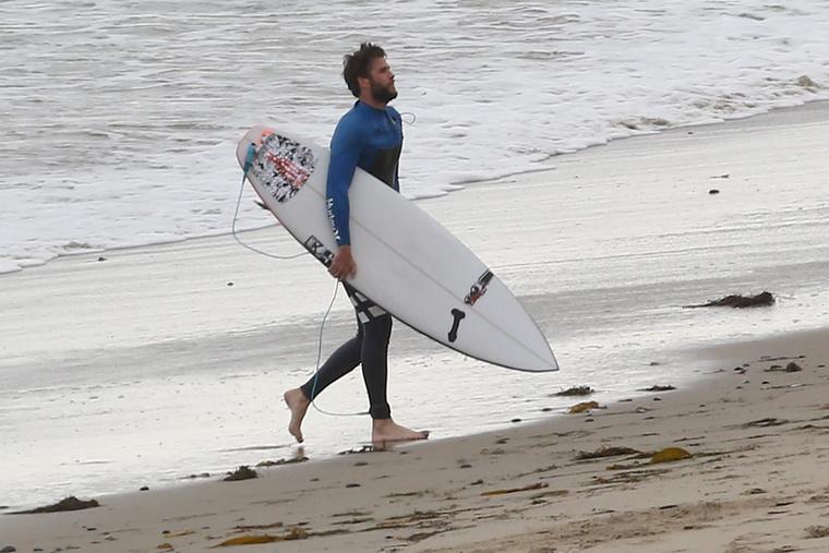 A pontosság érdekében közölnénk a képügynökség leírását is: Liam Hemsworth fagyos időben kapta el a hullámokat Malibuban, akár egy igazi szörfös arc