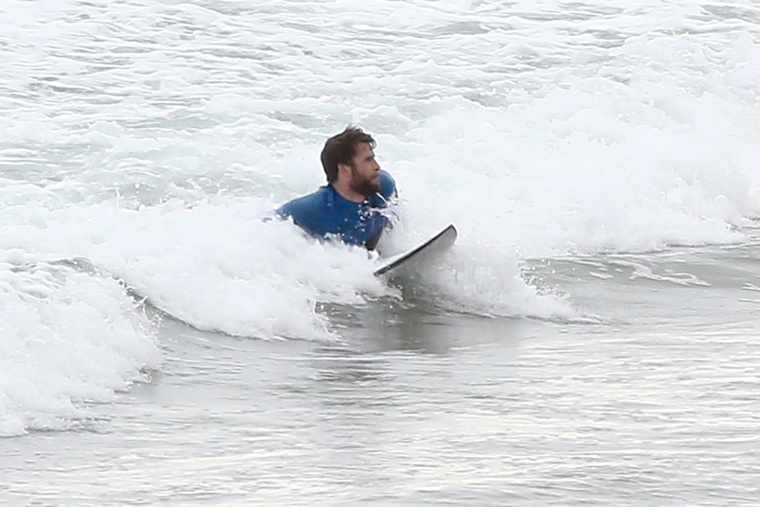 Fogta a deszkáját, lement a malibui partra, aztán beúszott