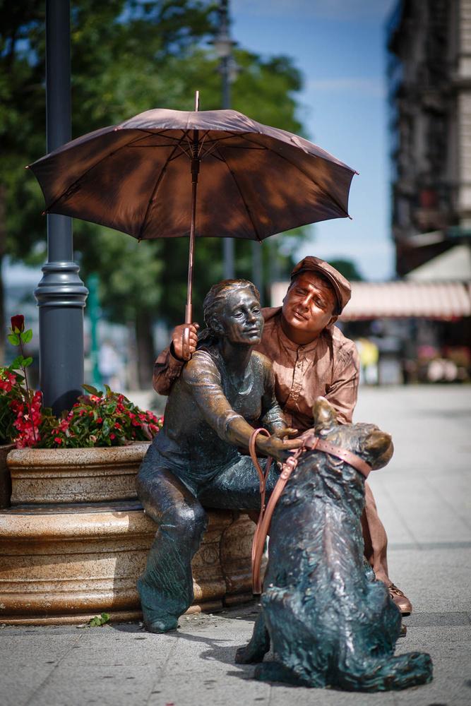 """Amely kampány végigjárta a várost, hogy a párra lelt szobrokat új társukkal együtt megörökítse, és megmutassa, hogy párkapcsolatban élni jó, és fontos, hogy kitartsunk egymás mellett akkor is, ha olykor az égig tudnánk felrugdalni a mi életünk drága, egyetlen szerelmét.A képen a Duna-korzó már csak félig magányosnak tekinthető szobra, a """"Kutyás"""" vezetéknevű lány találta meg a Nagy Őt."""