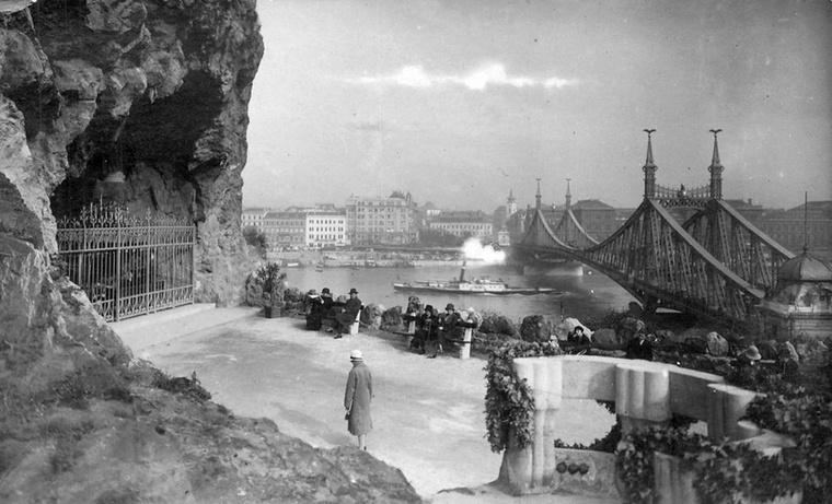 Sziklakápolna a Gellérthegy oldalában, háttérben a Ferenc József (Szabadság) híd.