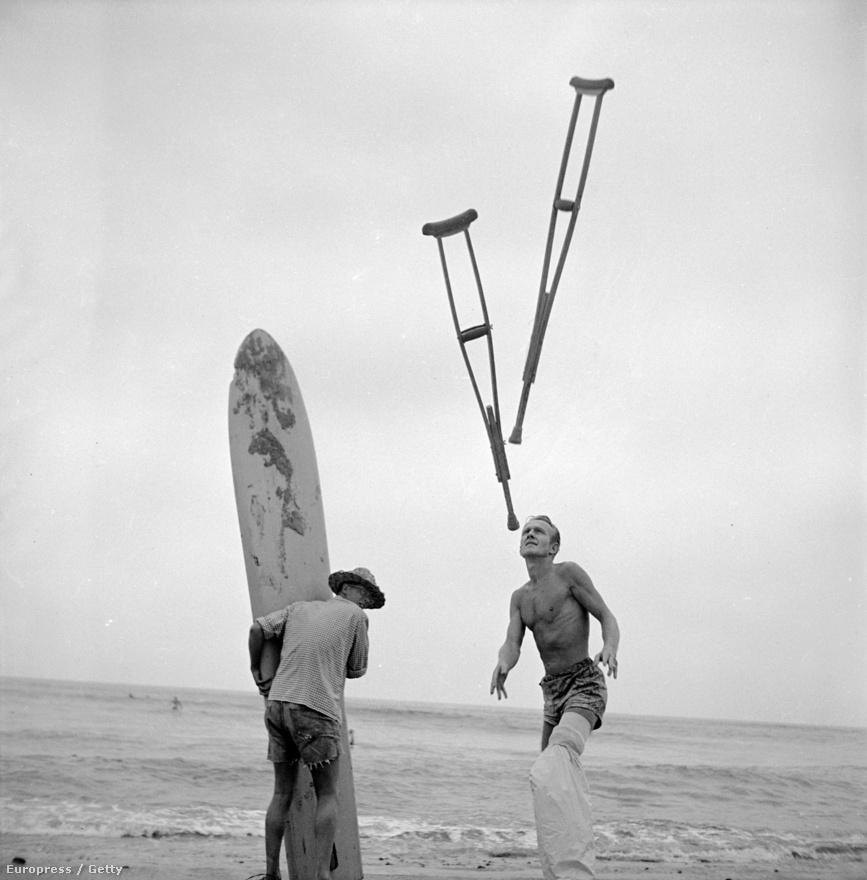 Jim Elliot, a sérült szörfös könnyed mozdulattal szabadul meg mankóitól, miközben segítőtársa a deszkáját tartja. Elliot lábát fólia fedi, hogy a gipszet ne érje víz, így hiába a lábtörés, a szörfözés nem marad el.