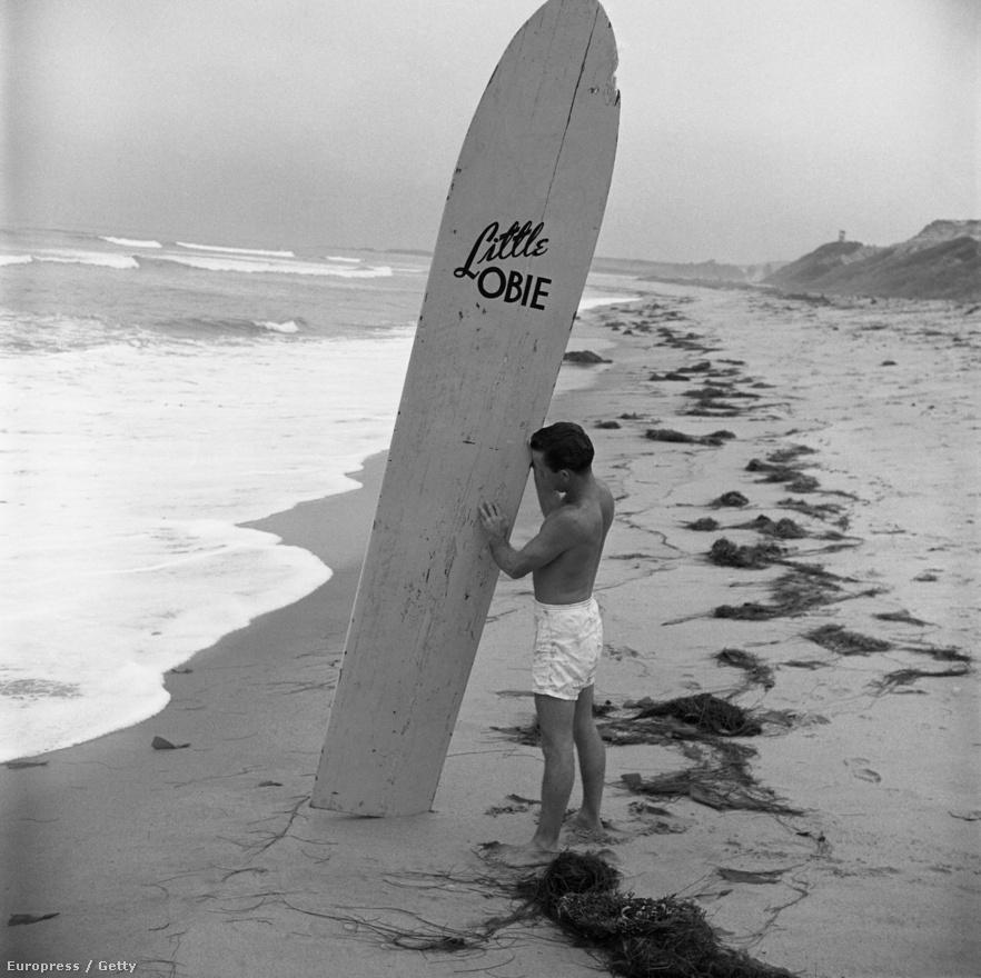 Obert Rod ismét: ezúttal a Kicsi Obie névre keresztelt imádott deszkáját megtávasztva áll a homokos parton és ellenőrzi annak állapotát, mielőtt nekivágna a hullámoknak.