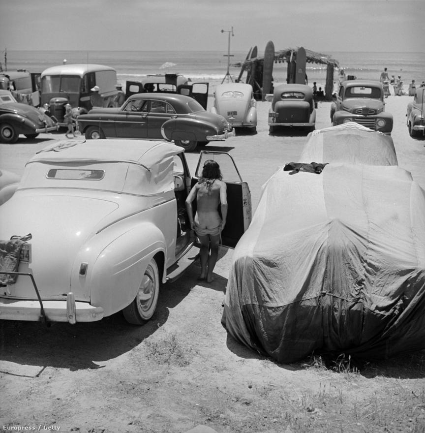 A fiatal lány két parkoló autó között veszi át fürdőruháját Kalifornia egyik legnépszerűbb strandján, San Onofre partjainál.