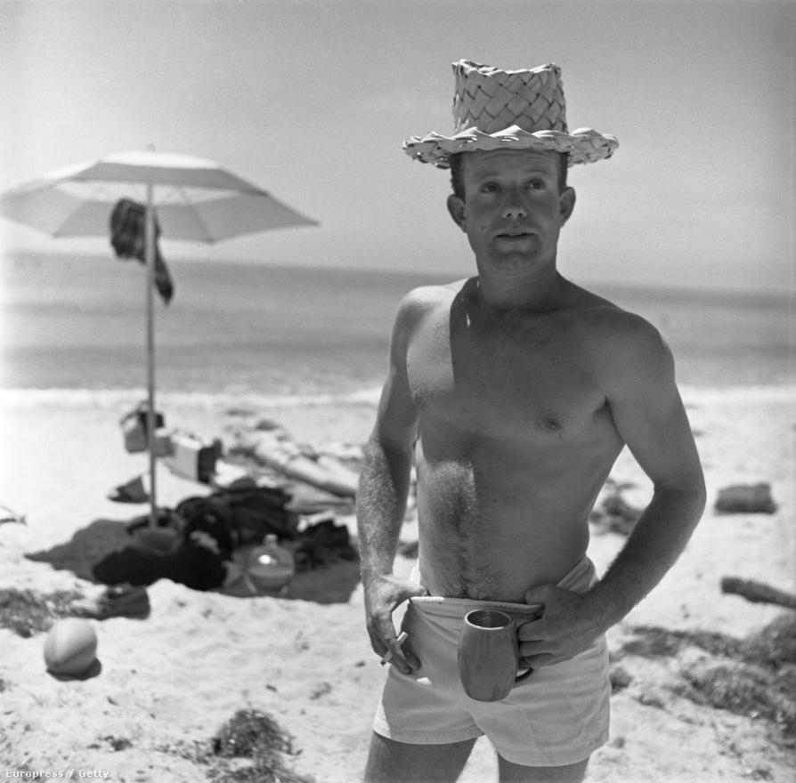 Obert Rod, az amerikai szörfös Kalifornia partjainál tökéletes pózba vágta magát.  Fején szalmakalap, egyik kezében bögre, másikban cigaretta, hüvelykujjai pedig az úszóshortja derékrészébe kapaszkodnak.