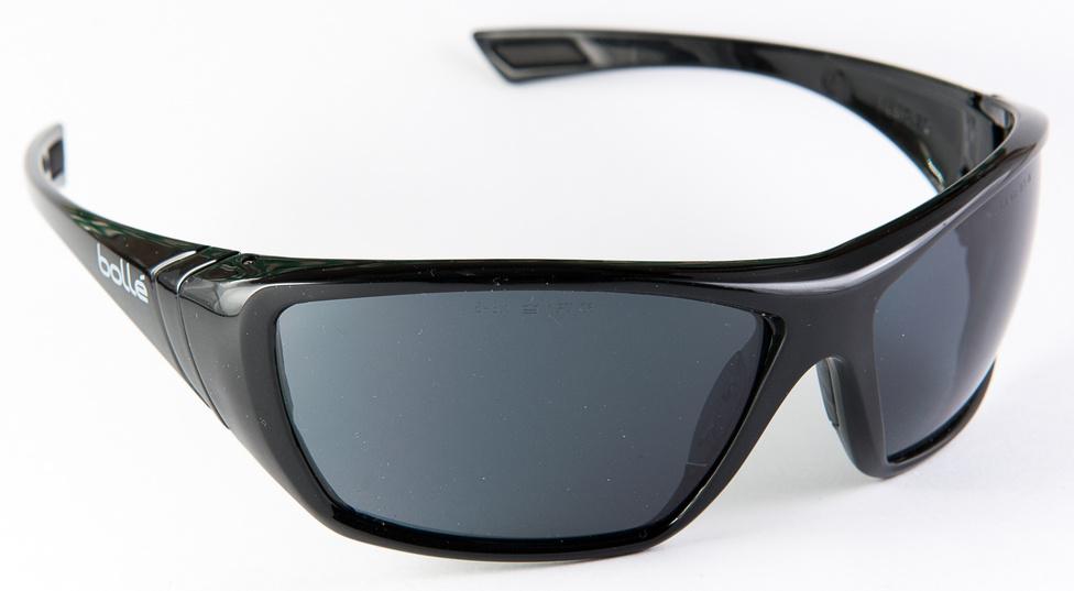 Bollé Hustler (31gramm, 3000+                         Azért kezdem ezzel, hogy akit nem érdekelnek a napszemüvegek, a trendek, és a stílus apró finomságai, azoknak ne kelljen tovább olvasniuk. Igen, vegyenek egy munkavédelmi napszemüveget egy munkavédelmi boltban. A Bollé a munkavédelmiek mezőnyében a drágábbak közé tartozik: 3 és 4 ezer forint között van. Nevetséges, mi? Pedig a munkavédelmi napszemüvegekre sokkal szigorúbb szabványok vonatkoznak. Mérettem már be munkavédelmi napszemüvegeket optikában, és az optikus a tökéletes UV-szűrésen nem is csodálkozott. Azon annál inkább, hogy milyen pazar a munkavédelmi napszemüvegek prizmakorrekciója - az ívelt lencse torzításának precíz anyagvastagsággal történő korrekciója. Bizony, ezek nem torzítanak, már az 1500 forintosak sem. Hogy miért ilyen olcsók? A nagy gyártók kevés modellt csinálnak, nincsenek szezononkénti frissítések, érdekes anyagok és színek, drágább üzletbérleti díjak, reklámköltség. Stump Bandi egy ilyenben motorozik, biciklizik és időnkét flexel már vagy két éve, és nem vigyáz rá, de a cucc meghökkentően jó állapotban van. Most, hogy egy Oakleymat elnyelte a tó, megfogadtam, hogy ezen túl csak munkavédelmi napszemüvegben szörfözök.